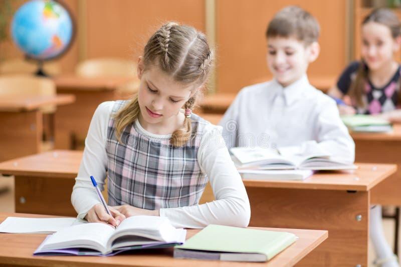 教育,学校,学会和儿童概念-学校哄骗与笔和课本写测试的小组在教室 免版税库存照片