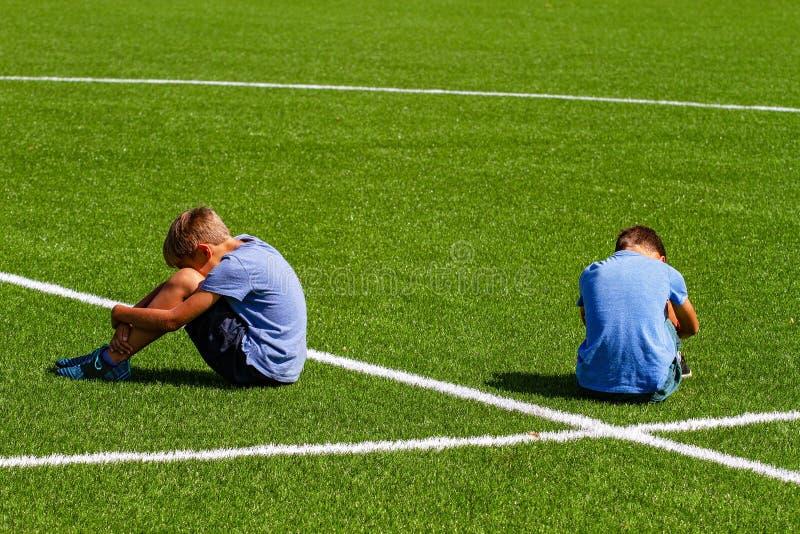 教育,胁迫,冲突、社会关系和人概念-紧接坐两个哀伤的失望的男孩  免版税库存图片