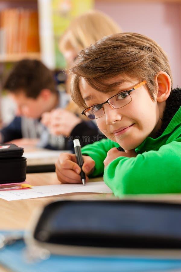 教育-学生在执行家庭作业的学校 库存图片