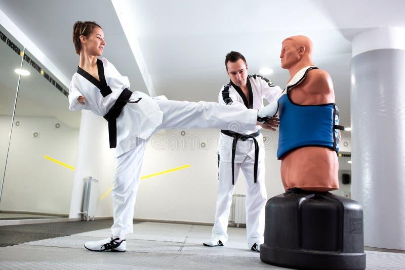 教跆拳道的老练的武道教练对他的学生以身体伤残 免版税库存图片