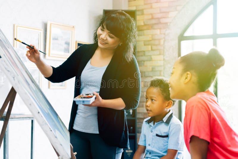 教黑孩子艺术的亚裔妇女 库存照片
