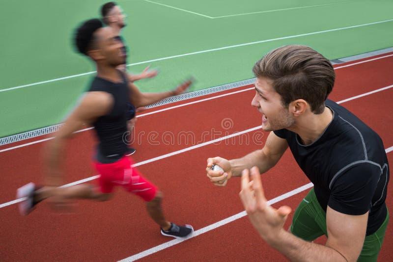 教练员叫喊的近的年轻不同种族的运动员人奔跑 免版税库存照片