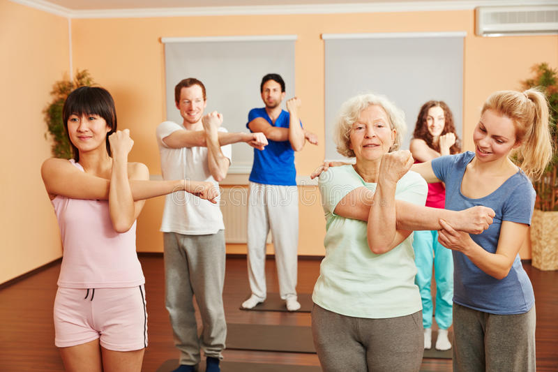 教练员帮助有瑜伽锻炼的资深妇女 免版税库存图片