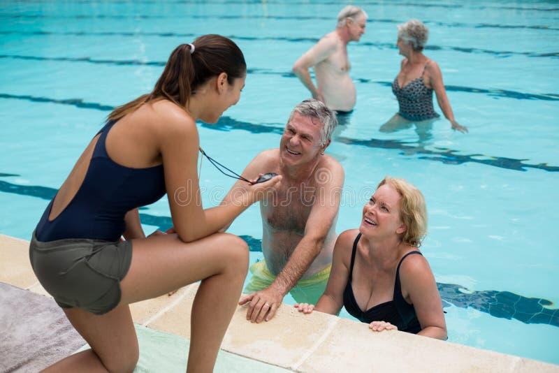 教练员谈论计时与资深游泳者在游泳池边 库存图片