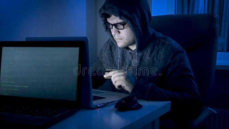 敞篷的男性黑客窃取从信用卡的金钱使用膝上型计算机 免版税库存图片