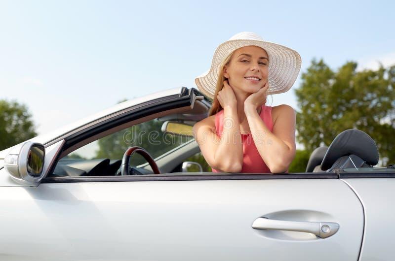 敞篷车汽车的愉快的少妇 免版税图库摄影