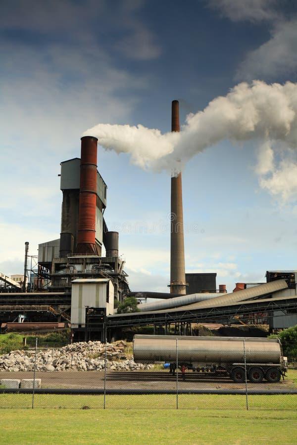 散发滚滚向前的毒性发烟的活跃钢铁厂精炼工 图库摄影
