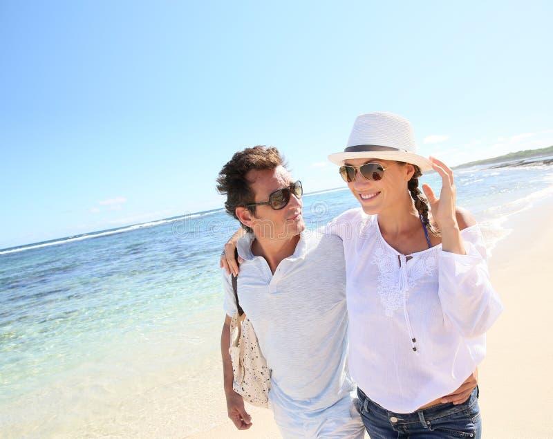 散步在海滩的现代愉快的夫妇 库存图片