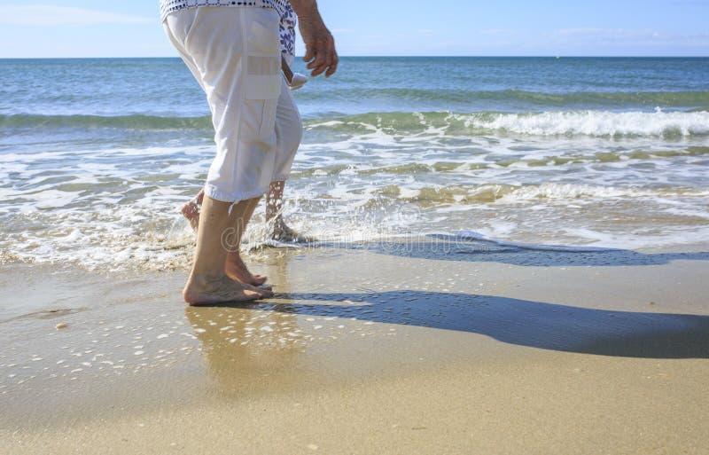 散步在海滩的老人 免版税库存图片