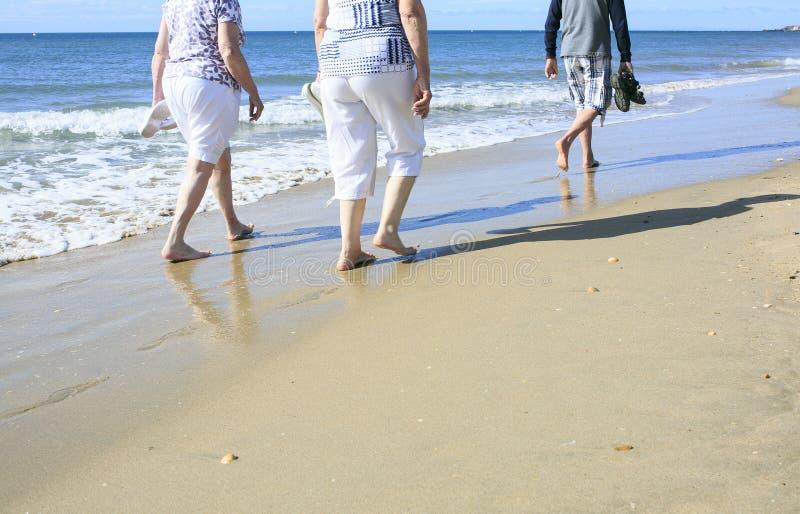 散步在海滩的老人 库存图片