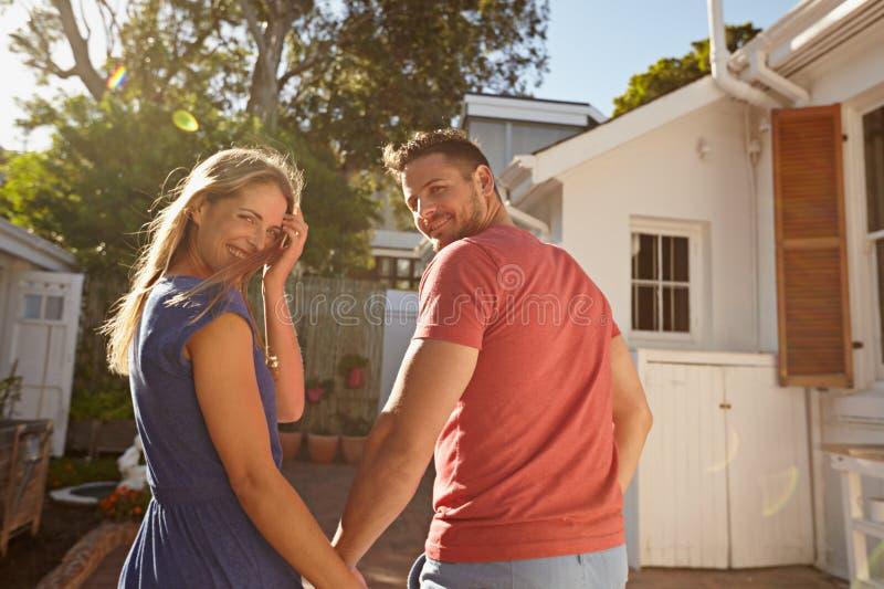 散步在他们的房子附近的年轻夫妇 免版税库存照片