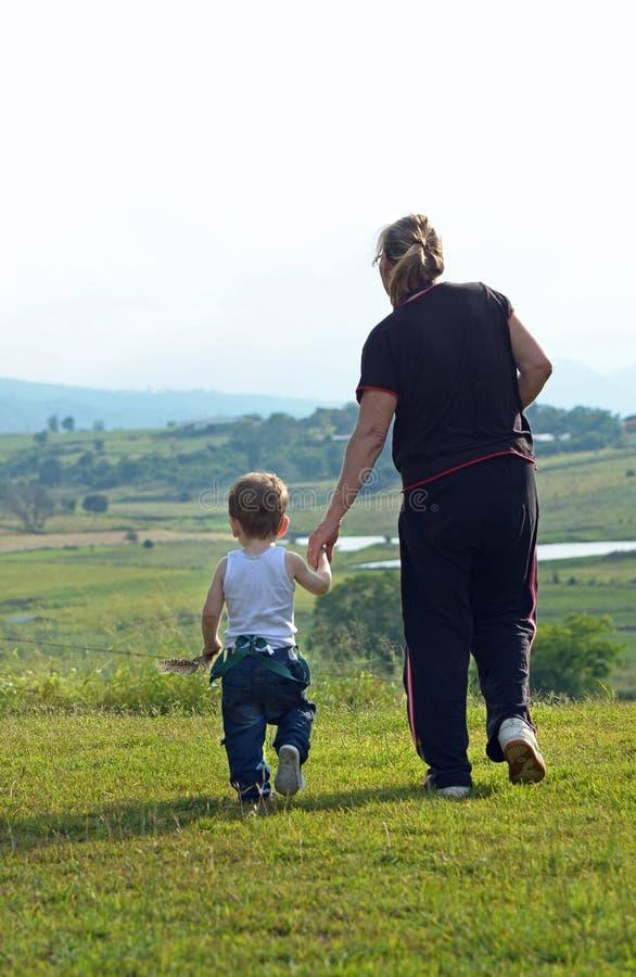 散步孙子的祖母在惊人的农村乡下 免版税图库摄影