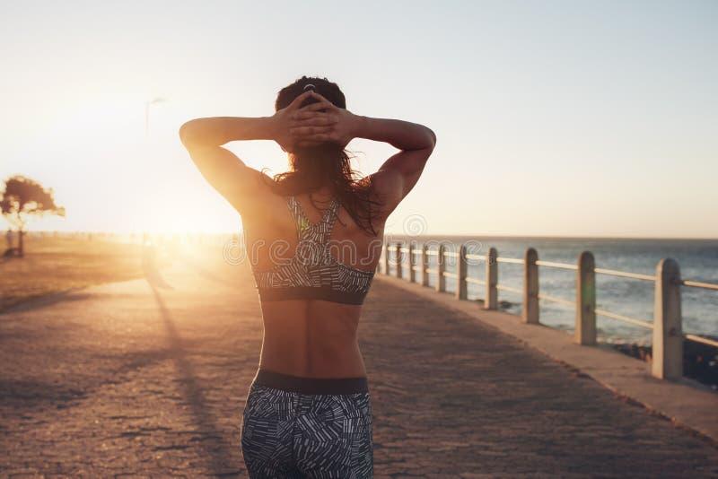 散步由海的女运动员在日落 库存照片