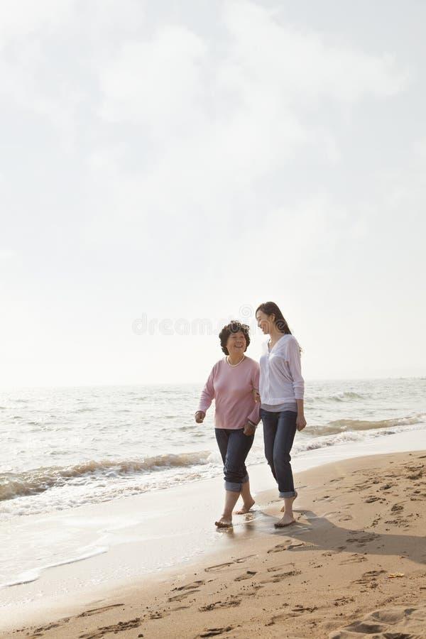 散步由海滩的祖母和孙女 免版税库存图片