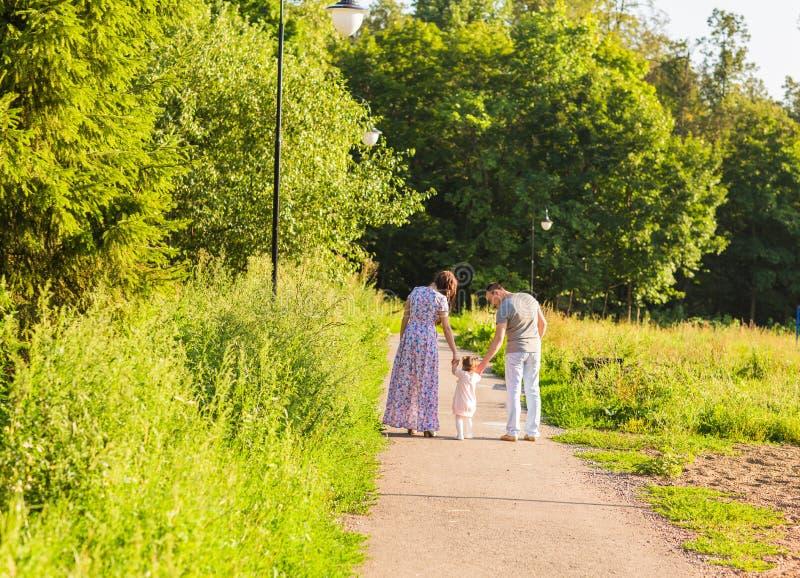 去散步的家庭背面图在夏天乡下 图库摄影