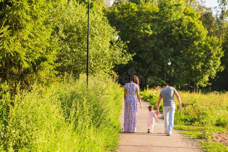 去散步的家庭背面图在夏天乡下 库存图片