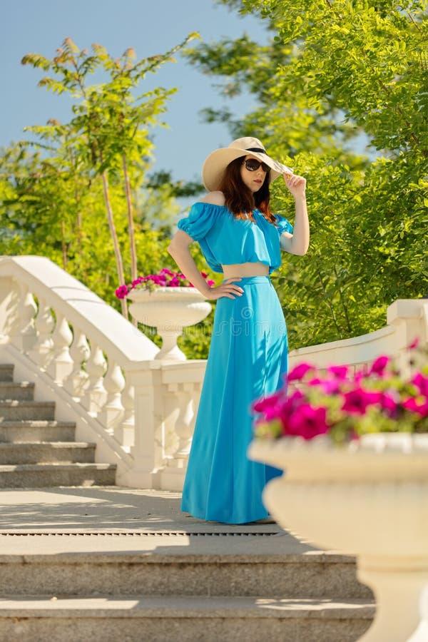 散步的年轻美丽的妇女在天蓝色的长的礼服 图库摄影