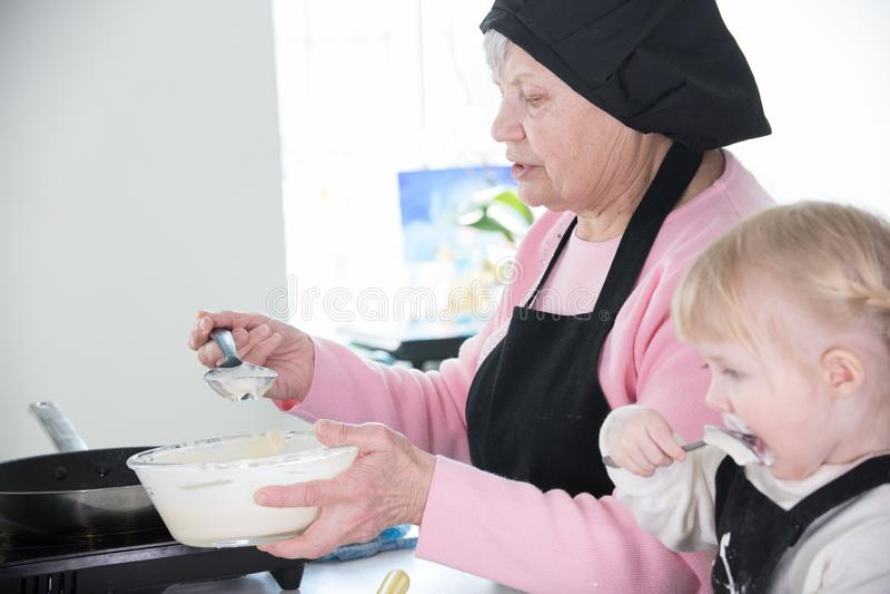散漫的女孩吃酸性稀奶油,当她的祖母在平底锅时投入了面团 库存图片