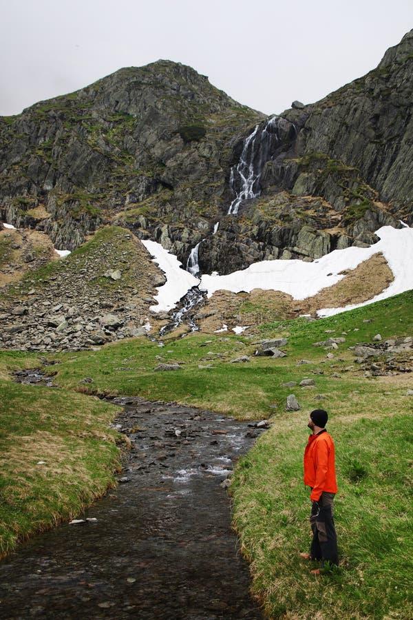 敬佩一个夏天山风景的年轻摄影师在Transylvanian阿尔卑斯,有一朵小的瀑布和多雨云彩的 免版税库存图片