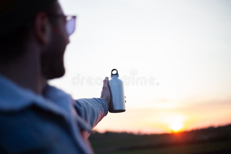 敬佩与钢瓶的年轻人日落在他的手上 免版税图库摄影