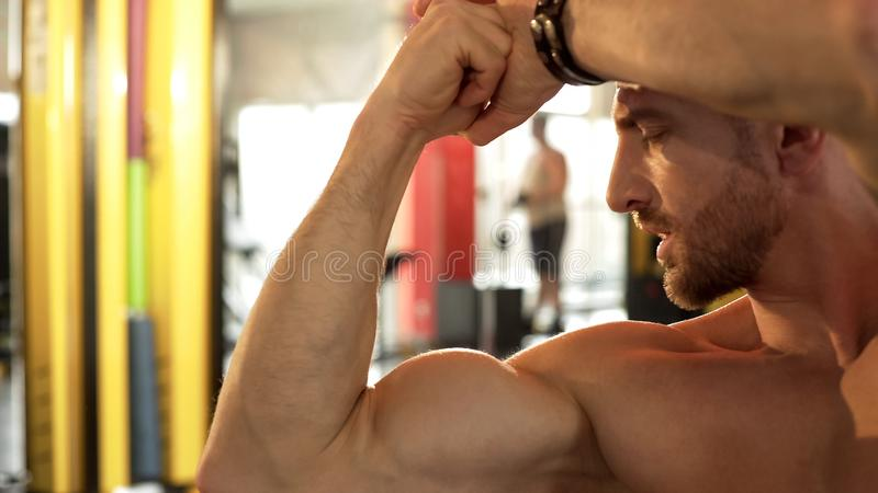 敬佩他的被发展的肌肉的适合的男性,做二头肌姿势健身房,感到骄傲为结果 库存图片