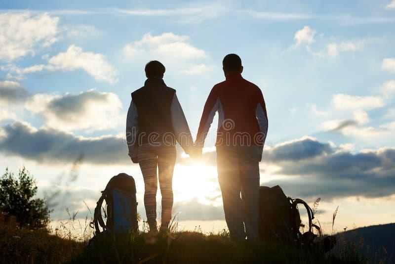 敬佩在山的后面观点的年轻人日落握手 免版税库存照片