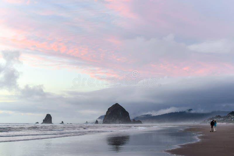敬佩干草堆岩石的恋人在日落 免版税库存图片