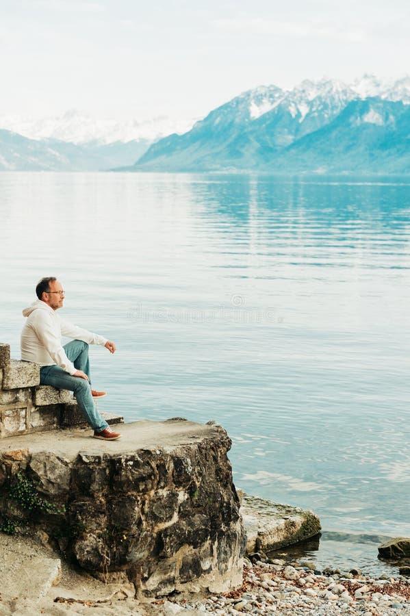 敬佩有山的帅哥画象美丽的湖 库存图片