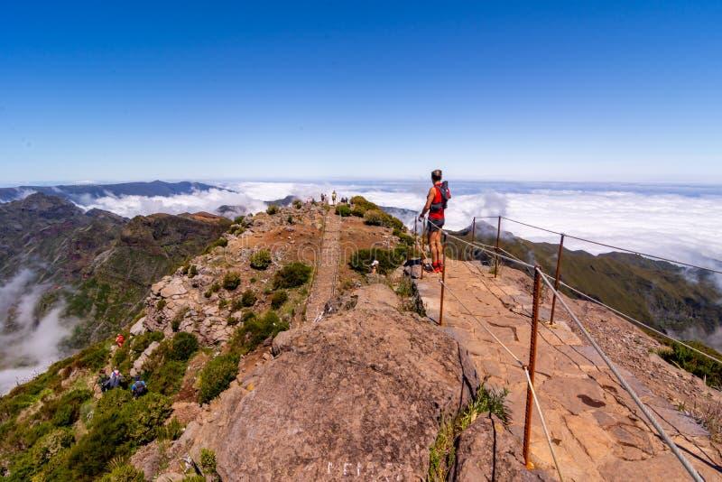 敬佩看法的小组徒步旅行者在皮库岛鲁伊沃峰顶,马德拉,葡萄牙 库存图片