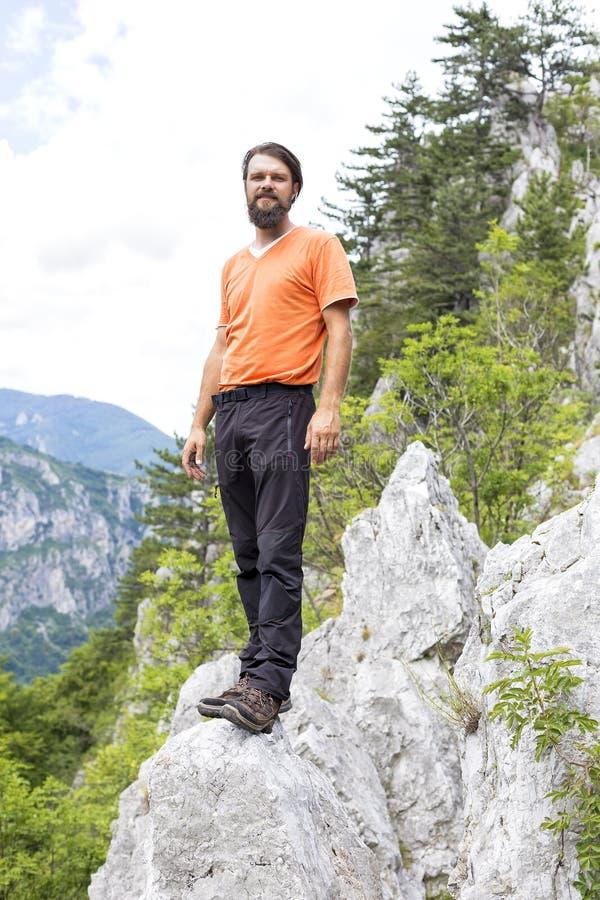 敬佩看法的年轻远足者从山的顶端 库存照片