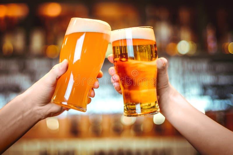 敬酒与杯的两个朋友低度黄啤酒在客栈 微粒的慕尼黑啤酒节的美好的背景 库存照片