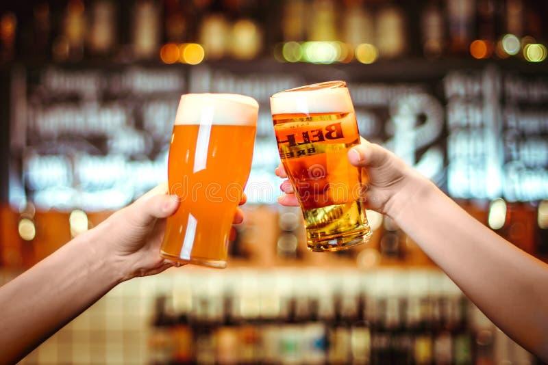 敬酒与杯的两个朋友低度黄啤酒在客栈 微粒的慕尼黑啤酒节的美好的背景 免版税库存图片