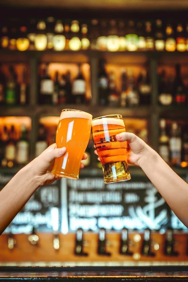 敬酒与杯的两个朋友低度黄啤酒在客栈 微粒的慕尼黑啤酒节的美好的背景 免版税图库摄影