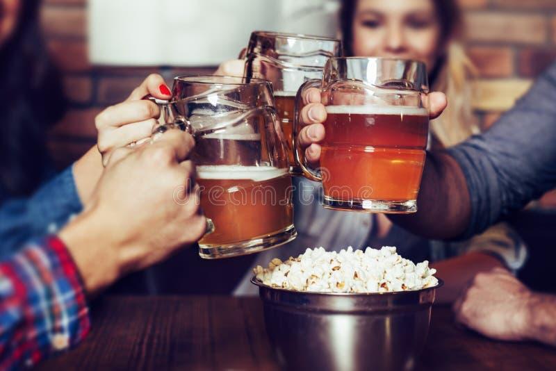 敬酒与杯的朋友低度黄啤酒在客栈-图象 免版税库存照片