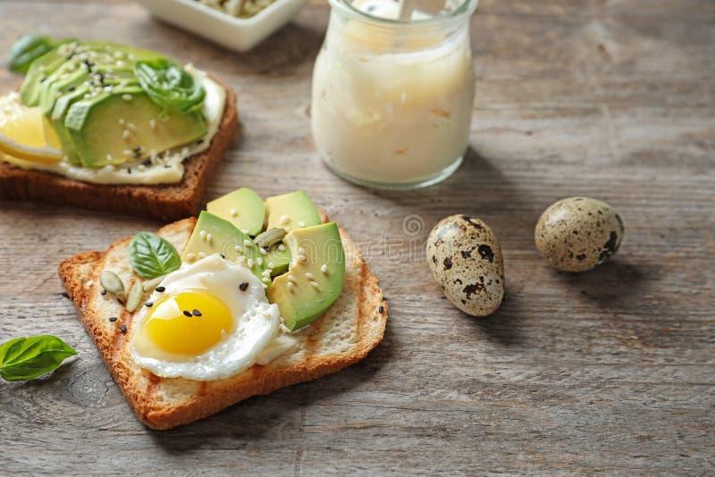 敬酒与煎蛋和鳄梨片的面包 免版税库存照片