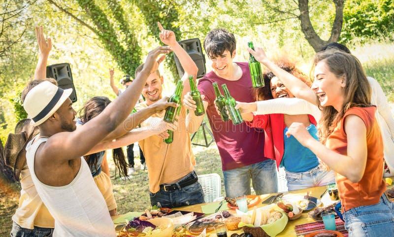 敬酒啤酒的年轻多种族朋友在烤肉游园会 图库摄影
