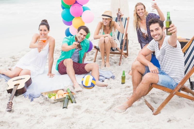 敬酒在海滩的小组朋友啤酒瓶 库存图片