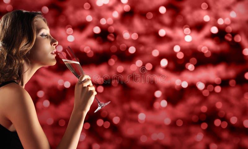 敬酒新年` s伊芙,在红色的妇女饮用的闪闪发光酒被弄脏的 图库摄影