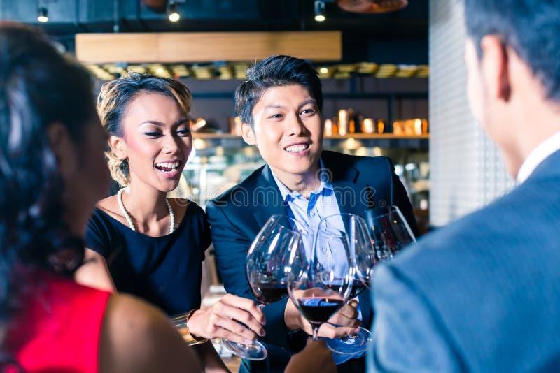 敬酒用在酒吧的红葡萄酒的亚裔朋友 库存图片
