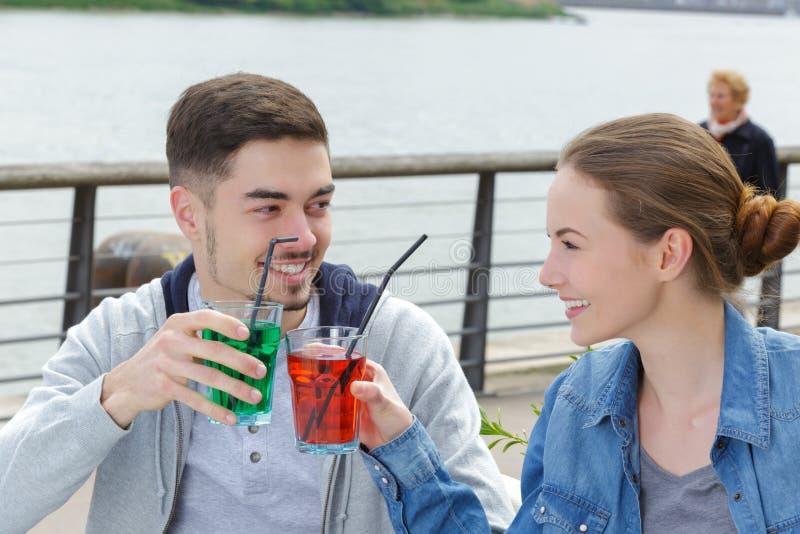 敬酒用甘露酒的年轻有吸引力的夫妇在酒吧大阳台 库存照片