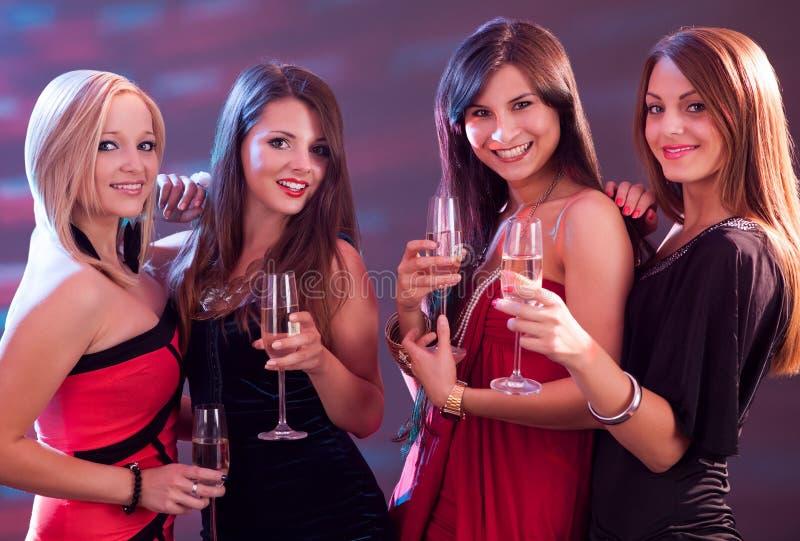 敬酒用香槟的时髦的妇女 免版税库存照片
