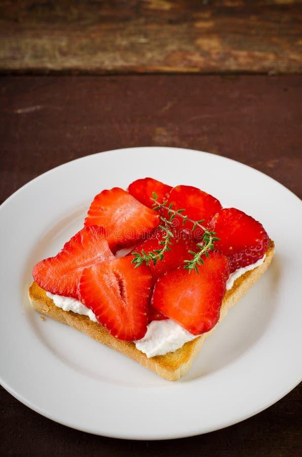 敬酒的面包用乳脂干酪、草莓和麝香草在木桌上 图库摄影