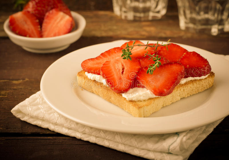 敬酒的面包用乳脂干酪、草莓和麝香草在木桌上 免版税库存图片