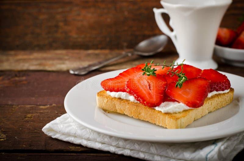 敬酒的面包用乳脂干酪、草莓和麝香草在木桌上 免版税库存照片