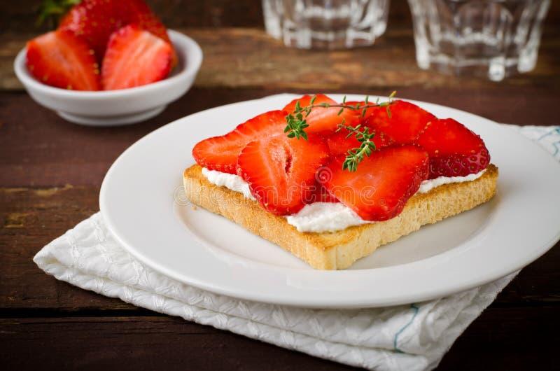 敬酒的面包用乳脂干酪、草莓和麝香草在木桌上 库存照片