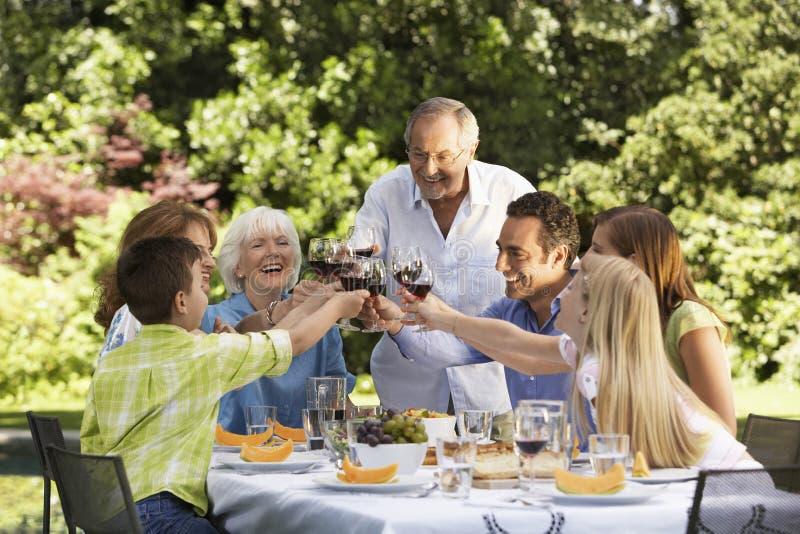 敬酒酒杯的家庭在表上在后院 免版税库存照片
