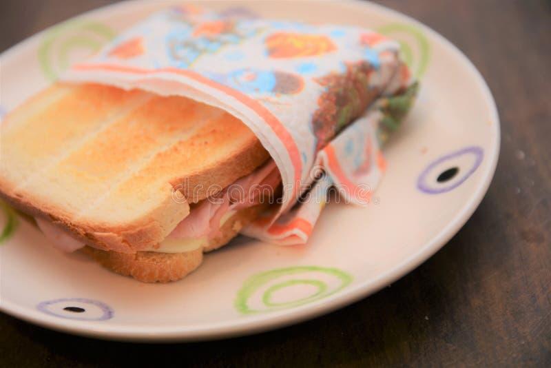 敬酒面包用火腿,并且乳酪点心便当吃在板材的营养快餐在桌上 免版税图库摄影
