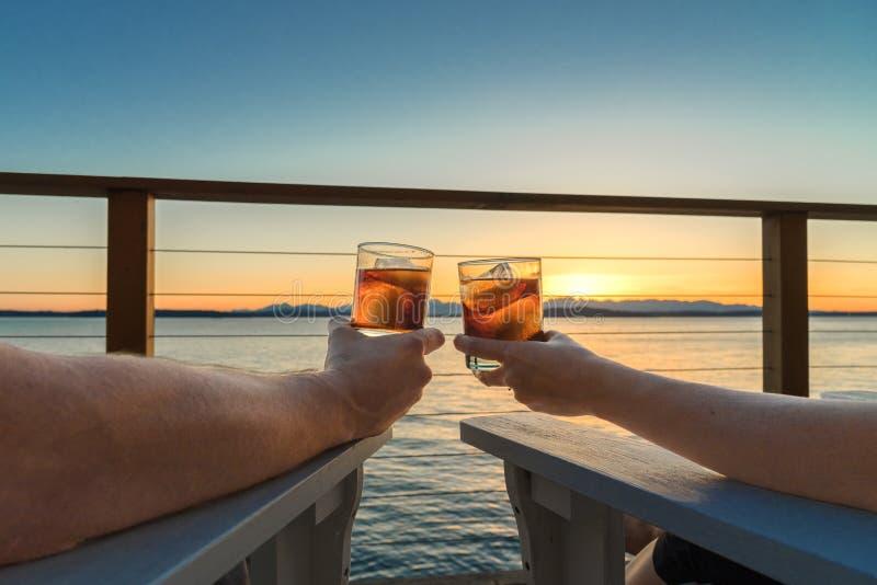 敬酒饮料海边的浪漫夫妇在日落 图库摄影