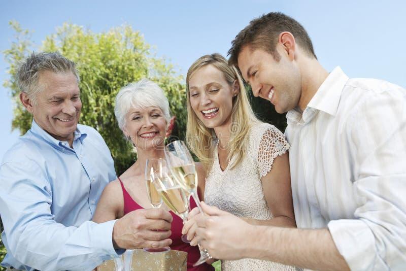 敬酒香槟槽的年轻和资深夫妇户外 免版税库存图片
