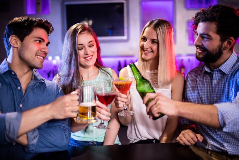 敬酒鸡尾酒、啤酒瓶和啤酒杯的小组朋友在酒吧柜台 免版税库存图片